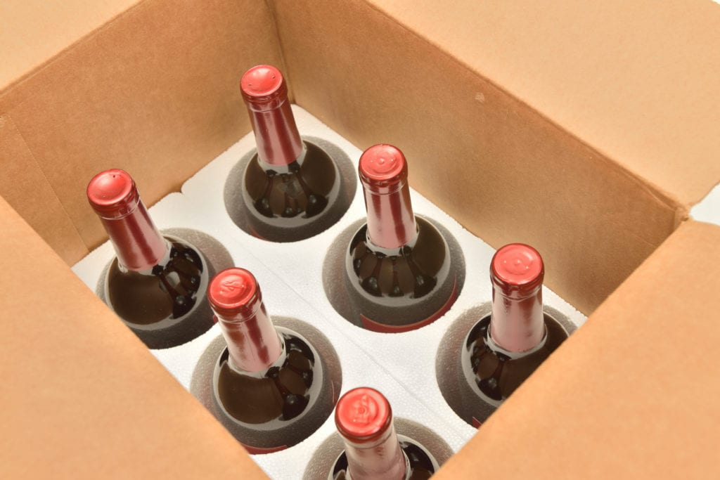 Six bottles of wine in a box being prepared for shipping after purchase online.