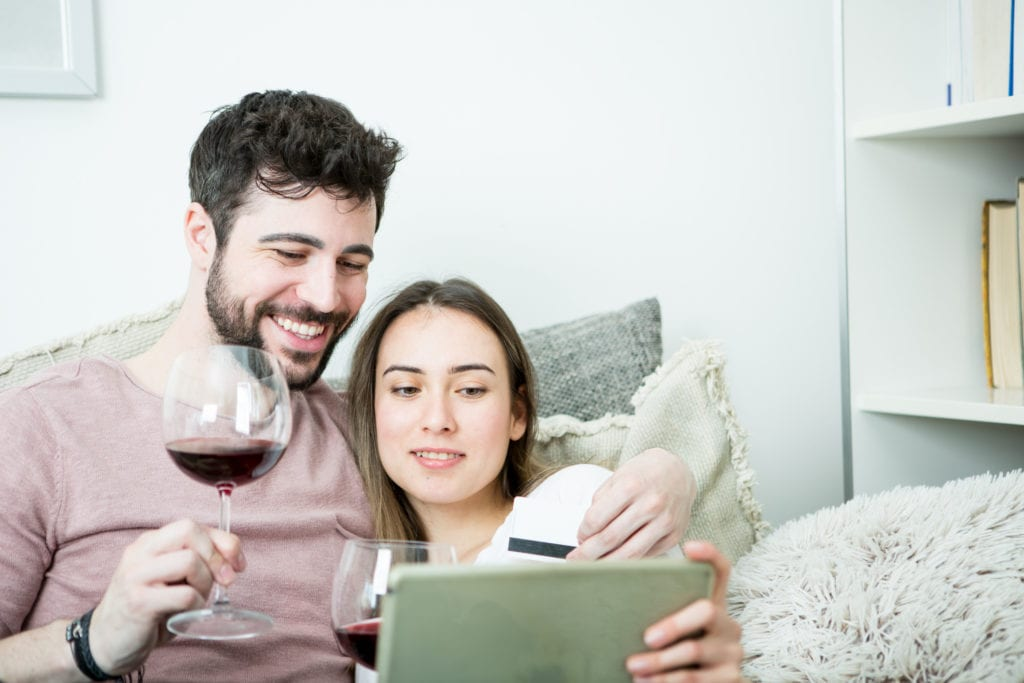 A couple sitting on their couch drinking red wine as they prepare to purchase wine online on their tablet.