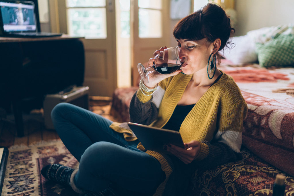 Young woman at home drinking red wine and using tablet to shop for wine online