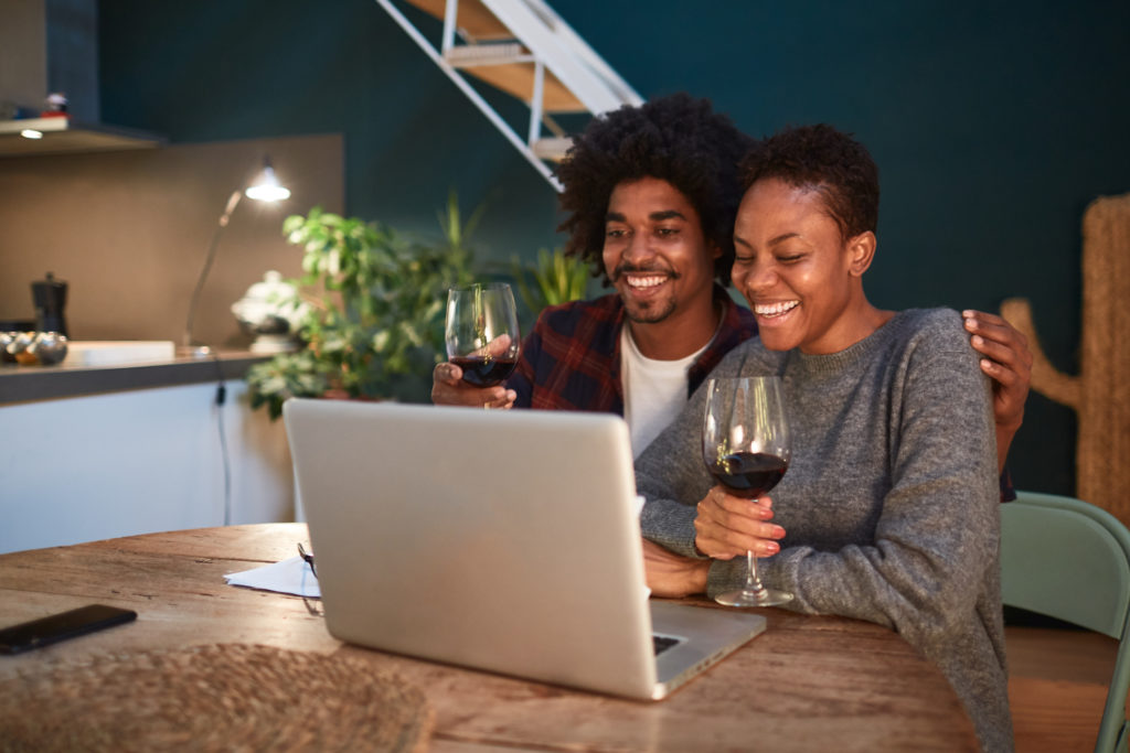 A millennial couple sitting in their kitchen and using their laptop to browse a winery website while drinking red wine.