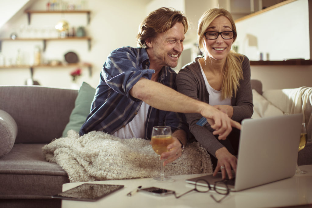 A couple sitting at home and shopping for wine online.