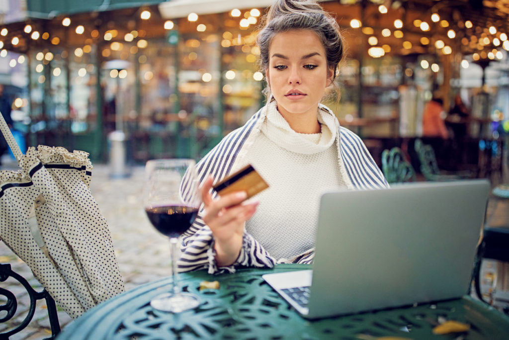 Young woman is shopping for wine online using her credit card and laptop in a rainy day