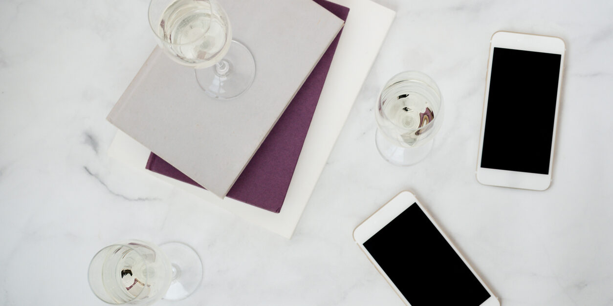 Wine glass on top of books and iPhones